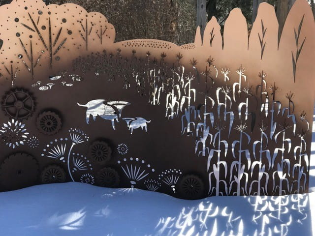 A metal plat with corn, cow and flower siloueetes cut out allowing the sun to stream through projecting the images onto the snow