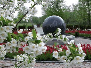 A large black globe on a pedastool surrounded by a circular stine path and bed of red flowers
