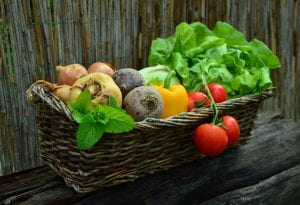 Wicker basket full of lettuce, tomatoes, peppers, beets, turnips,onions and a sprig of mint
