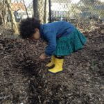 A small child in a jean shirt, teal skirt and bright yellow rain boots put seeds in the ground