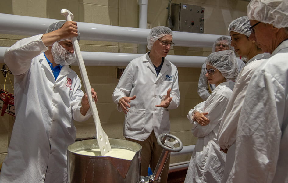 A group in white lab coats attending a dairy product demonstration.