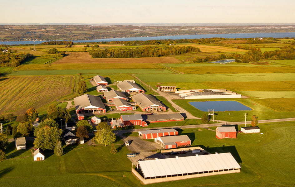 An aerial view of farm buildings near the one of the Finger Lakes.