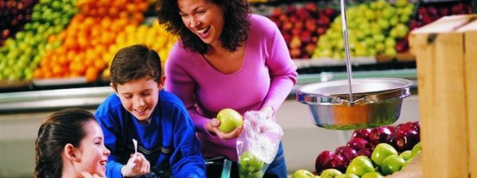mother with two children in the produce aisle of a grocery store