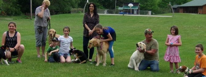 seven youth posing with their dogs and adult mentors