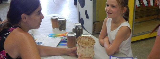 youth speaking with judge about a basket they wove to enter at the fair during project evaluation at the county fair