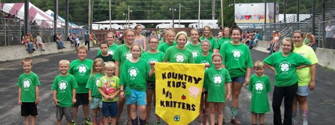 Kountry Kids and Critters participating in the 4-H parade with their banner and all wearing matching 4-H shirts.