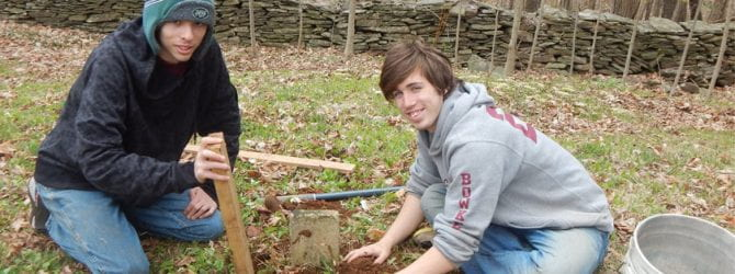 two youth resetting a crooked foot stone in a small cemetery