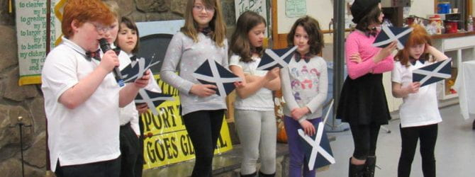 group of youth holding construction paper flags of Scotland as they read facts from a notecard.
