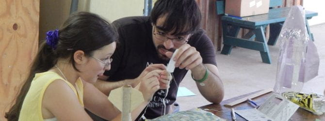 youth working with counselor to attach recovery string to nose cone while building a model rocket kit