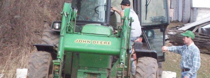 youth climbing up into the cab of a tractor under the supervision of instructor
