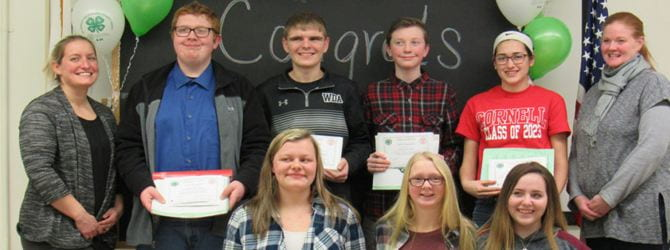 group of seven youth posing in a group with certificates they received alongside two adults: 4-H educator and 4-H issue committee member