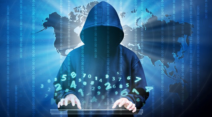 Cyber Crime image of man in hood over keyboard