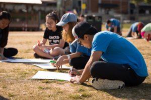 International students sit on ground working