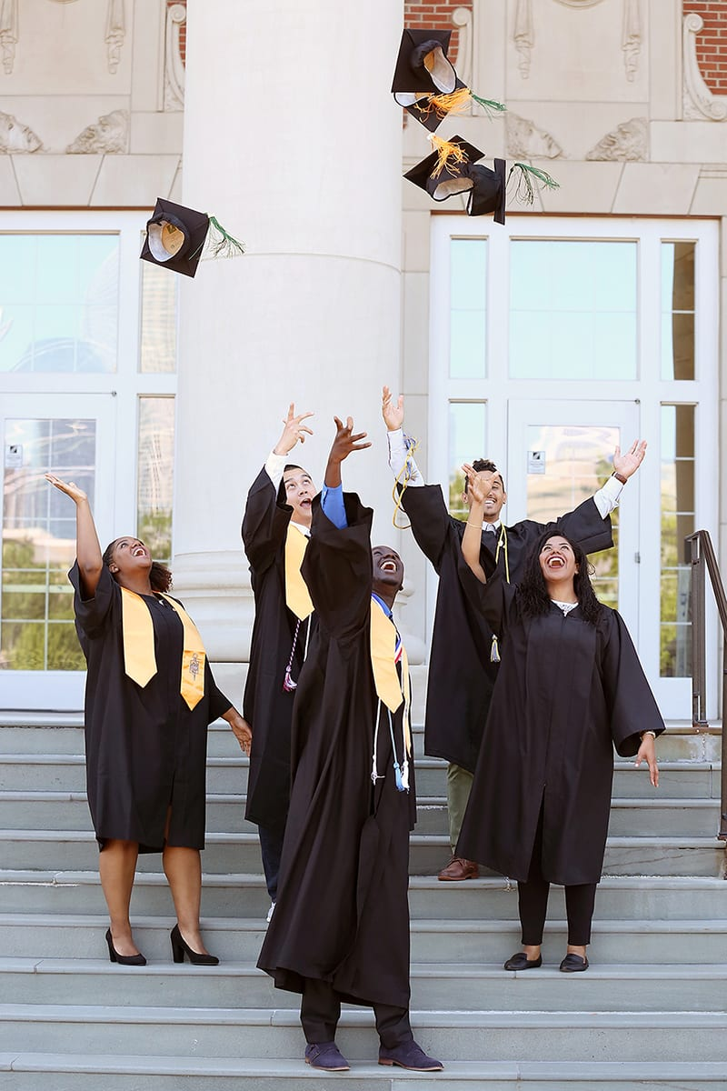 graduates throwing caps into air