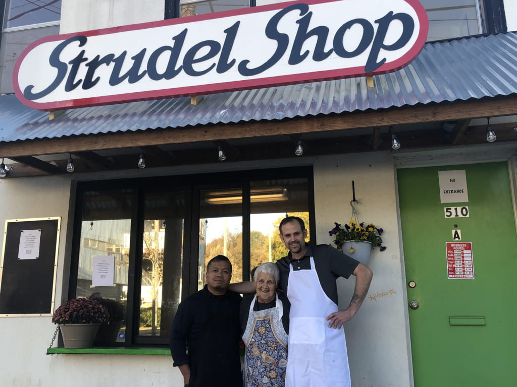 Three people stand outside strudel shop