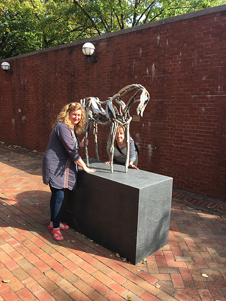 "Ceramics instructor Paula Smith and Chair Mary Kilburn pose with Deborah Butterfield's ""Lunalilo"", a steel sculpture of a small horse at Weatherspoon Art Museum, University of North Carolina-Greensboro."