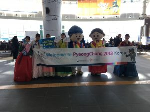 People holding welcome PyeongChang 2018 sign