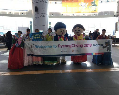 People holding welcome PyeongChang 2018 sign