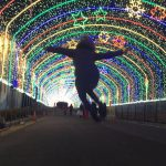 girl jumping in tunnel of lights
