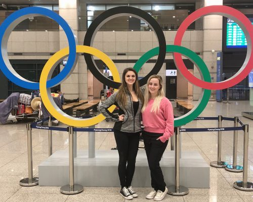 Two girls in front of Olympic rings