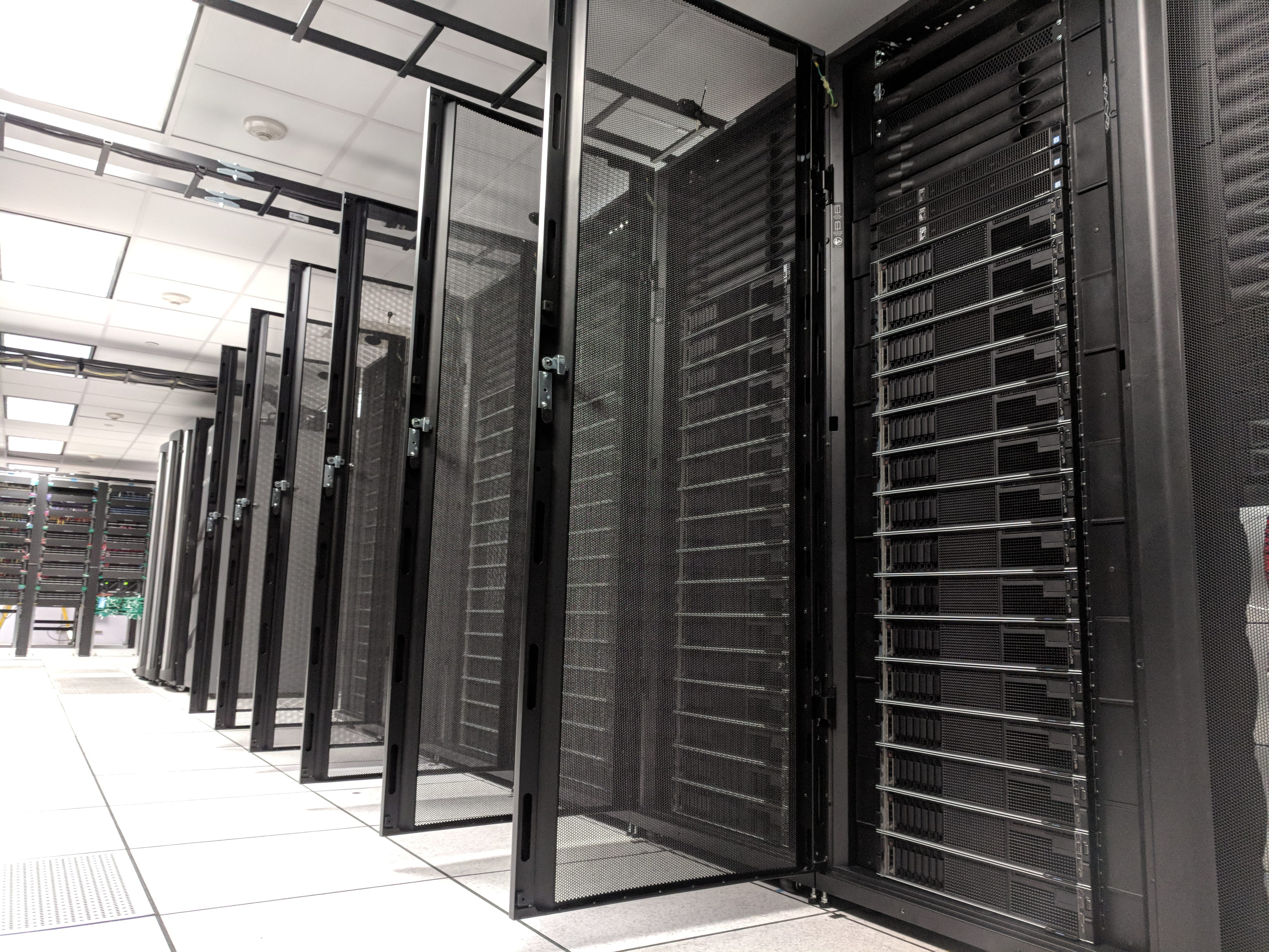 Ground level view of server racks with doors open showing servers in a row