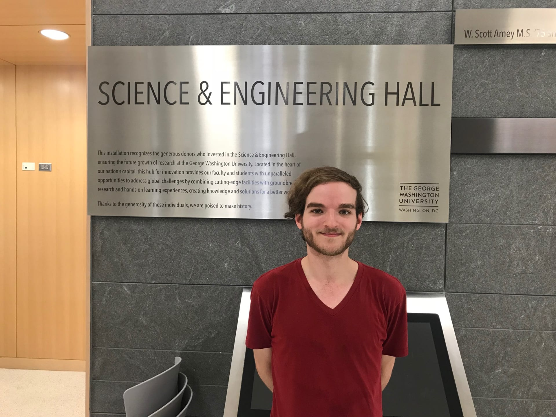 "Image of William Bonnett posing for a photo in front of ""Science & Engineering Hall"" Metal Sign"