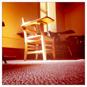 Sunlit chair in old classroom
