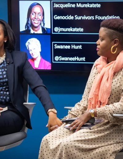 Panelist speaks holding another panelist's hand at How Women Saved Rwanda event