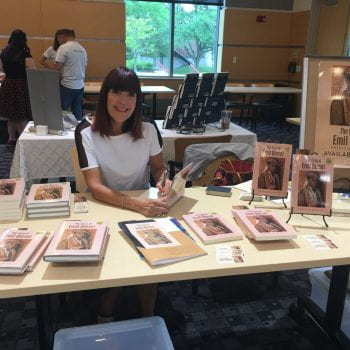 Patricia Scangas at a table selling her novel