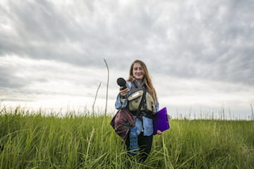 Courtney Sexton in field holding camera
