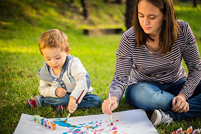 child_and_adult_painting_outside_1