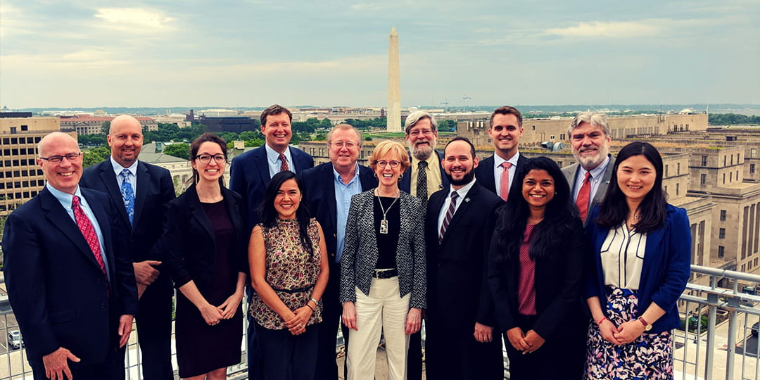 Staff and faculty of the GW Regulatory Studies Center standing on a rooftop with the Washington Monument in the background