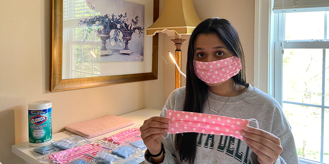 CCAS Student Leisha Mahajan holds up a mask that she made during COVID-19 pandemic