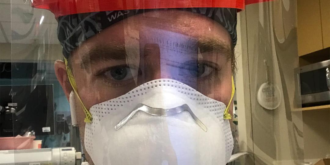 Dr. Luke Frey wearing a face helmet & a n95 mask