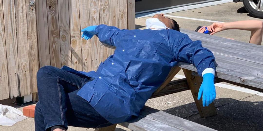 Sathya Prakash Harihar takes a nap on a picnic table while wearing lab attire