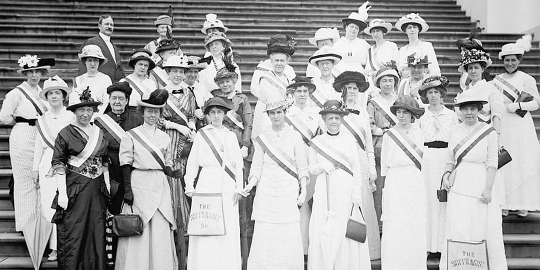 A group of suffragists standing in front of the US Capitol
