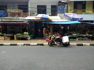 A Jakarta road with a motorcycle before some storefronts
