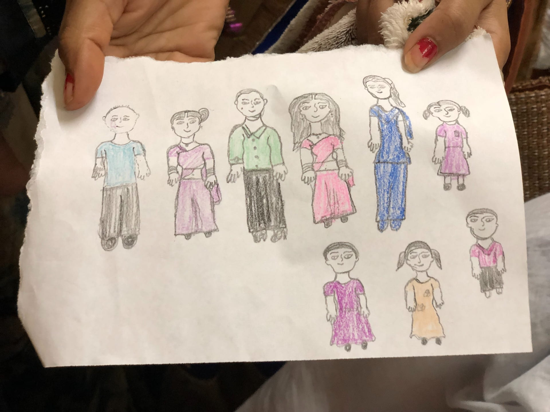 Drawing a family depicting a young girl in a purple dress, a woman in a blue sari and skirt, a, a woman in a pink sari and skirt, a man in a green shirt and black slacks, a woman in a light purple sari and skirt, a man in a blue shirt and black slacks, a young boy in a purple shirt and black pants, a young girl in a yellow dress, and a young girl in a dark purple dress