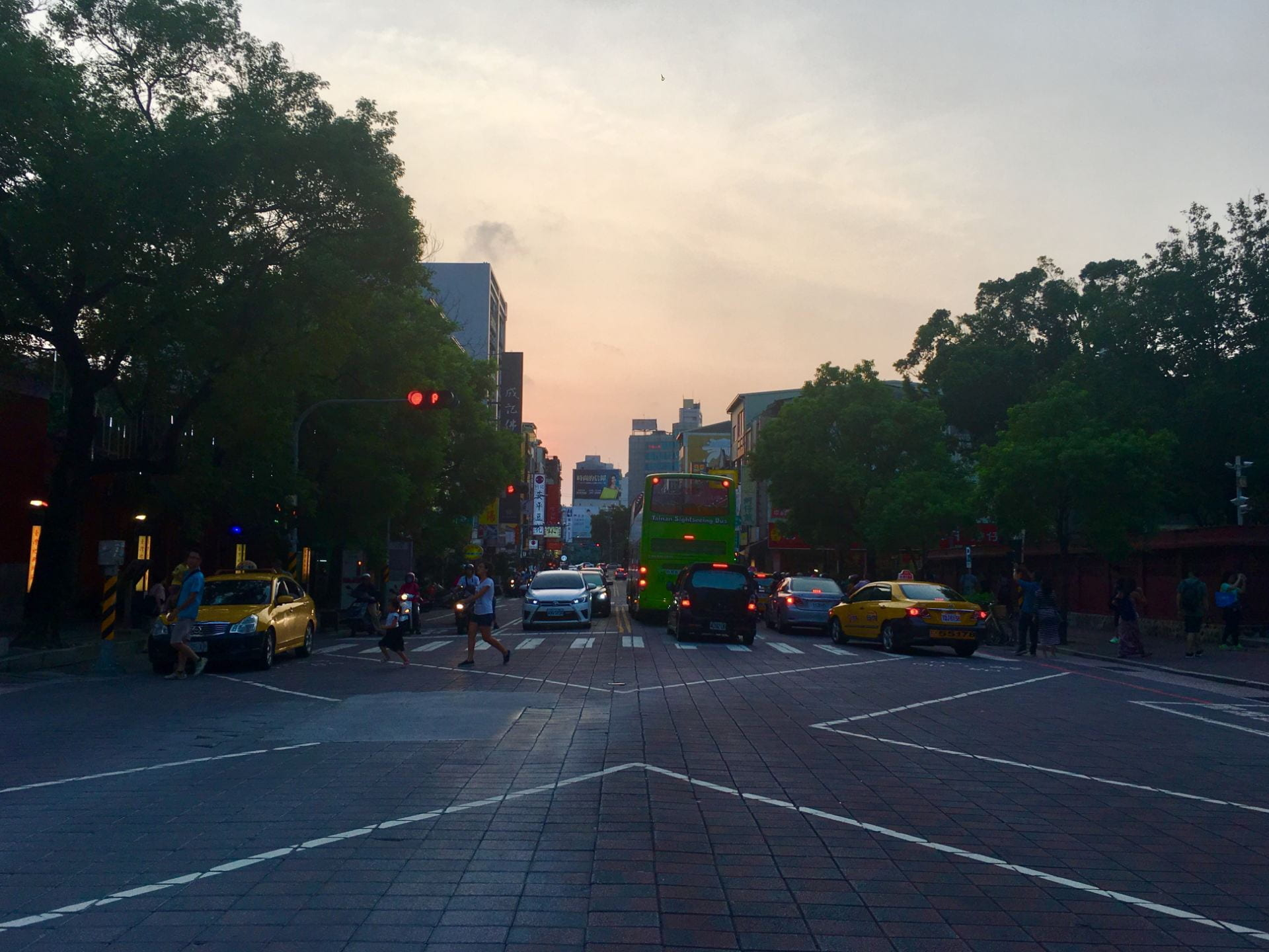 A crowd crosses a busy intersection lined with cars in Tainan as the sun sets