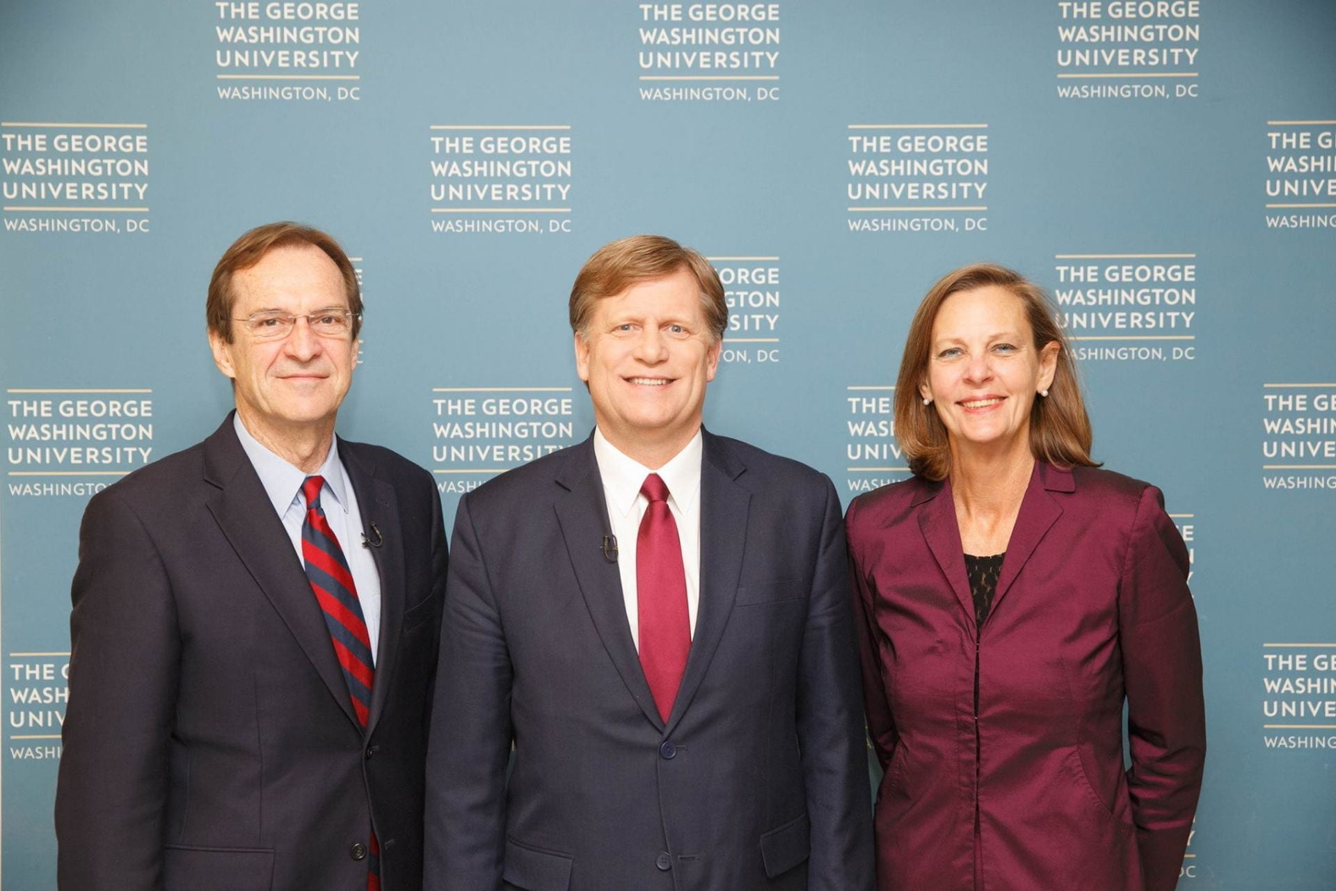 Three people standing in front of George Washington University step-repeat backdrop