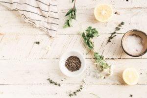 Various herbs, lemon, and salt on a white table.
