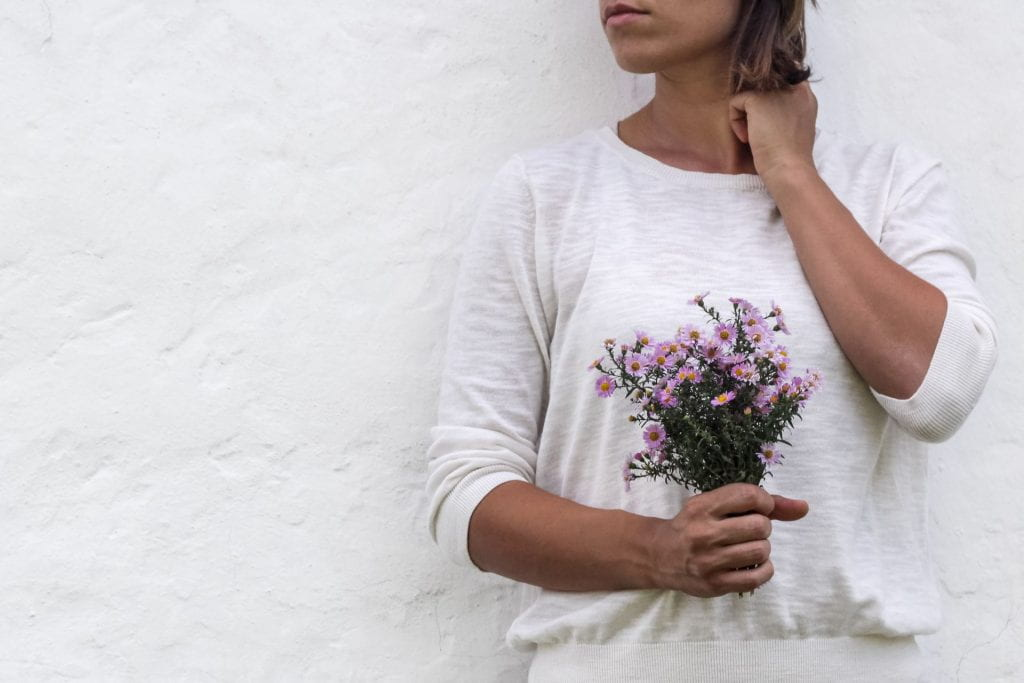 Woman standing in front of a wall holding flowers.