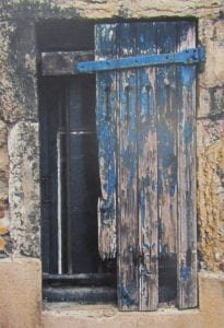 Photo of a weathered, blue shutter set in a stone wall.