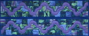 "Multicolored rectangular quilt in purple, blue, and green tones. Titled ""Drunkard's Path,"" created by Velma Jordan."
