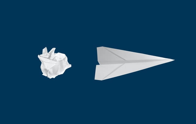Crumpled paper and a paper airplane on a dark blue background