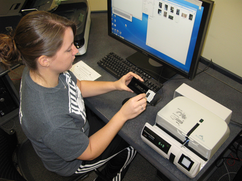 Student using the slide scanner in the Media Development Center, 213 Hale Library