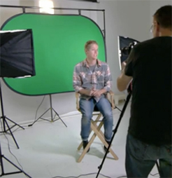 Smaller green screen with male sitting on chair in front of screen