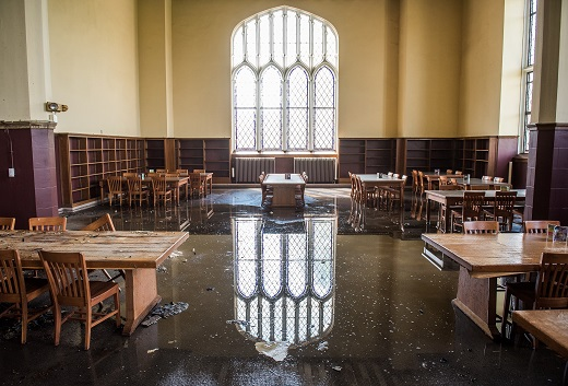 A stained glass window is reflected off of the standing water on the Great Room's floor.