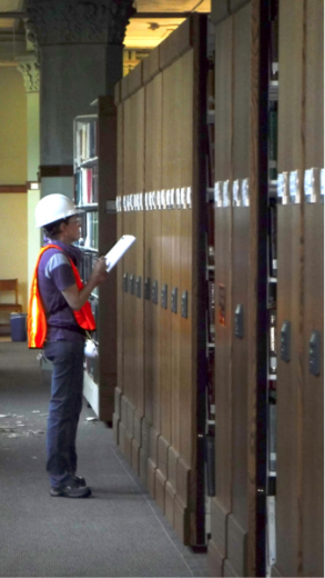 A women in an orange vest and a white hard hat is inspecting the brown compact shelves.