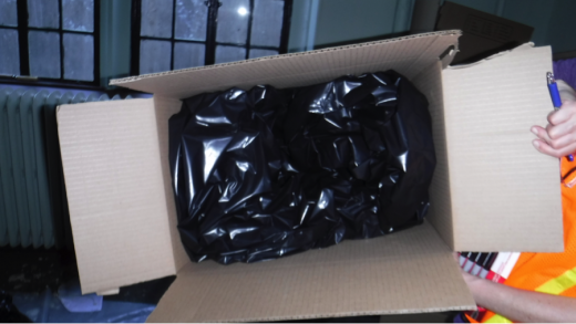 A large cardboard box lined with heavy black plastic is ready to be filled with wet books.